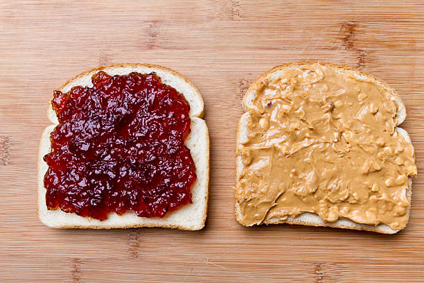 open face peanut butter and jelly sandwich - pindakaas stockfoto's en -beelden