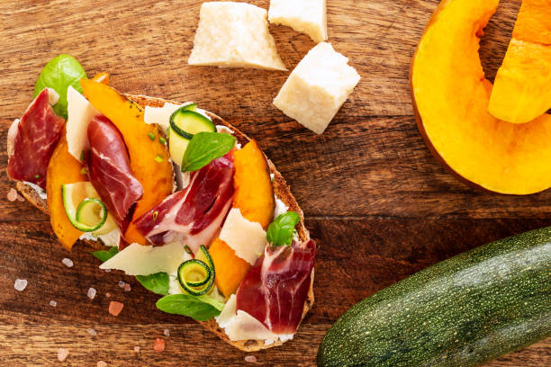 Open faced sandwich with iberico ham, parmesan and goat cheese, zucchini, pumpkin, basil and chives on sourdough bread. All on rustic chopping board, aside parmesan, pink salt, zucchini and pumpkin. stock photo