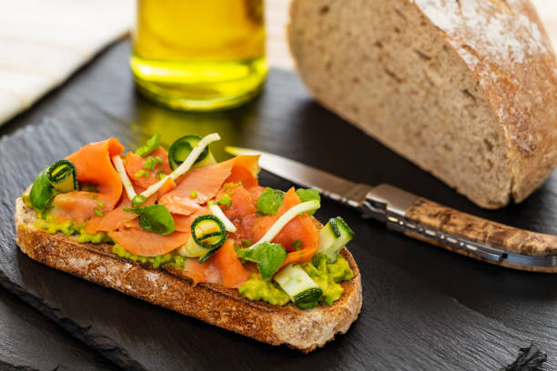 Open faced sandwich with smoked salmon, avocado, apple, zucchini, pumpkin, basil and chives on toasted sourdough bread. With knife, bread loaf and olive oil on slates. stock photo