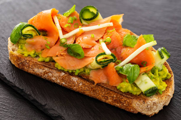 Open faced sandwich with smoked salmon, avocado, apple, zucchini, pumpkin, basil and chives on toasted sourdough bread. Displayed on slates. stock photo