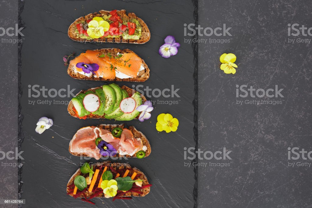 Open faced sandwiches with edible flowers stock photo