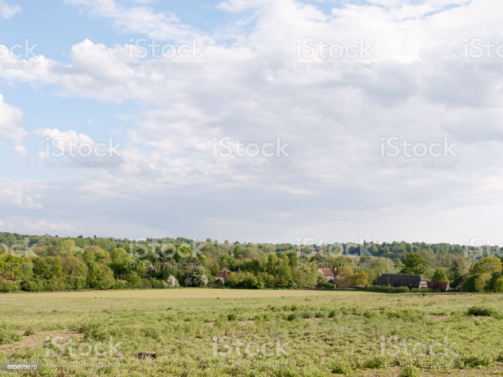 open farmland with houses in the distance outside in the country in essex england dedham in the uk on a bright a sunny day with lots of lush green royalty-free stock photo