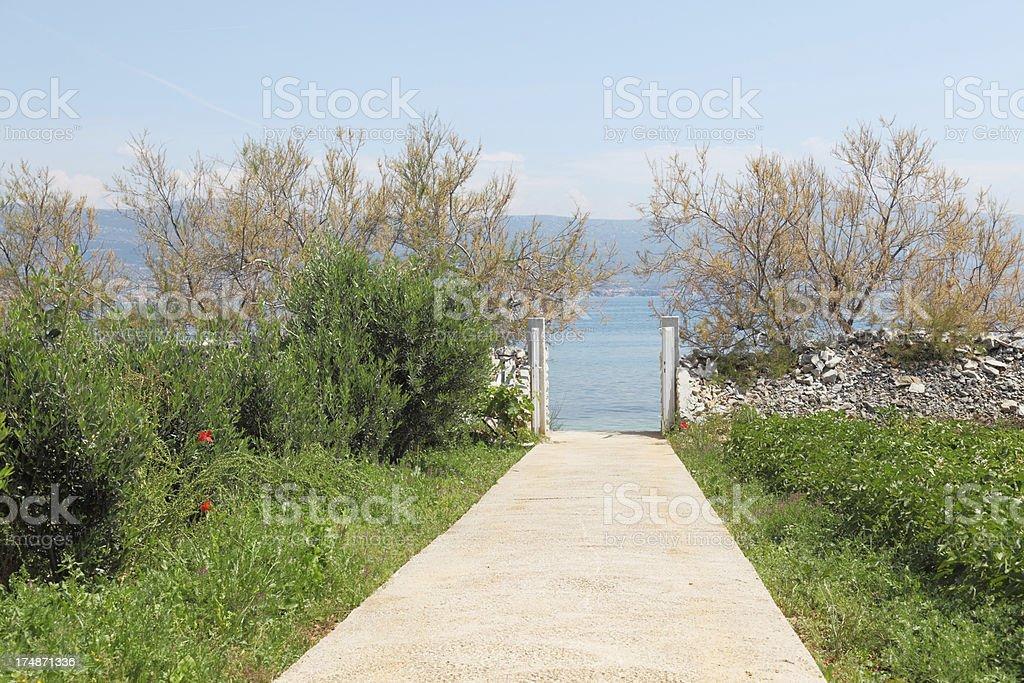 open fence with gate to turqouise mediteranean ocean Trogir Croatia royalty-free stock photo