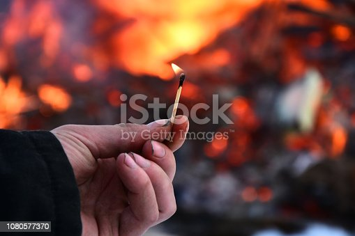 An image of a man's hand holding an open flame with a large fire in the background.