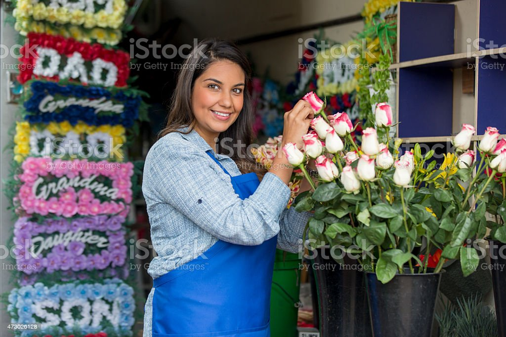 Smiling, handsome, Hispanic small business flower shop owner standing...
