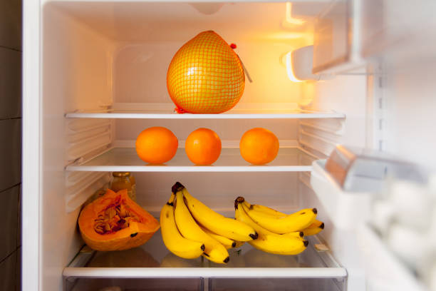 Open fridge with orange and yellow fruit inside on white shelves. The concept of a healthy diet. stock photo