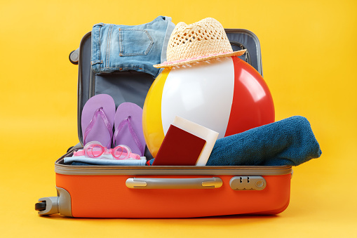 istock Open full suitcase with items for relaxation on a yellow background 1210686033