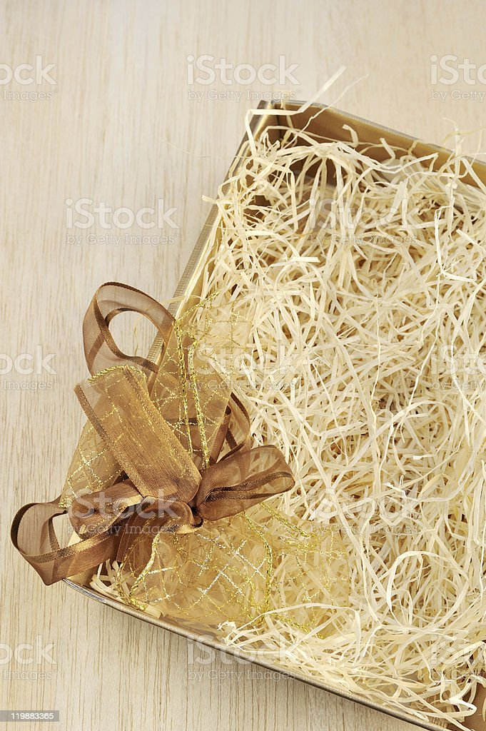 Open gift box and bow - filled with packing bast royalty-free stock photo
