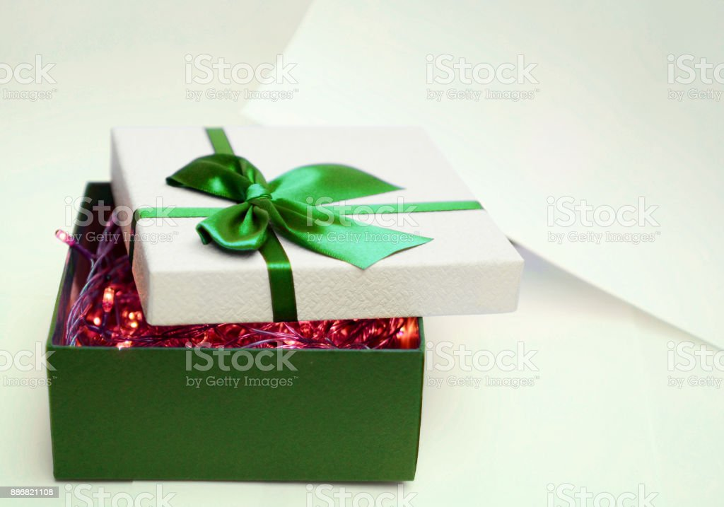 Open Gift Box With Green Ribbon And Small Red Lights In Bow One White Paper Isolated On