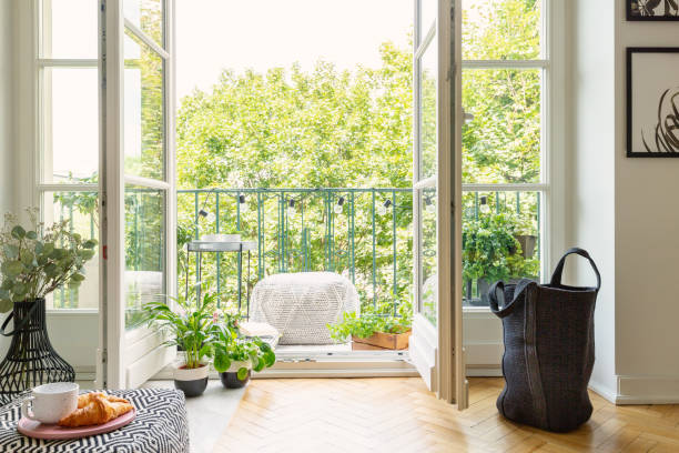 Open glass door from a living room interior into a city garden on a sunny balcony with green plants and comfy furniture stock photo