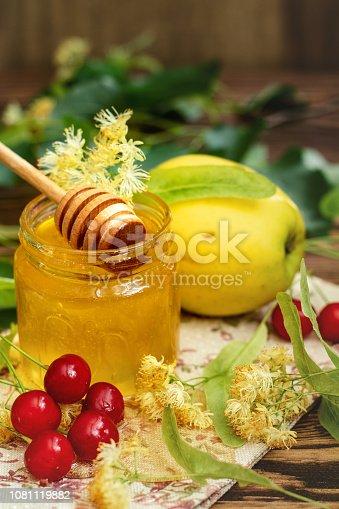 istock Open glass jar of liquid honey, apple and honey dipper, bunch of linden flowers 1081119882