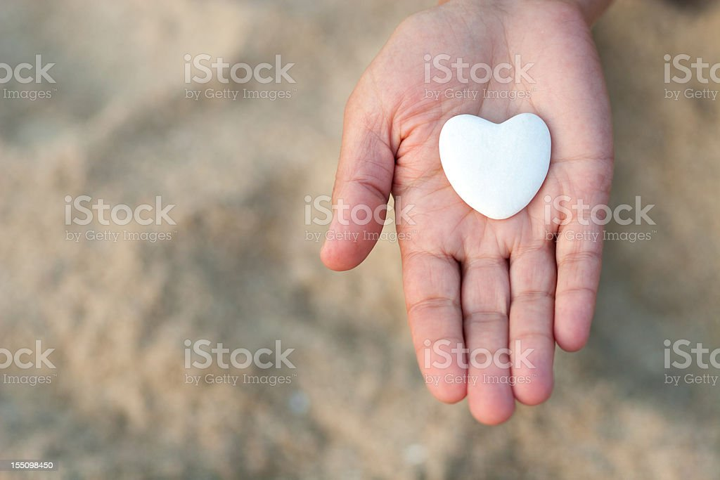 Open hand holding a heart on defocused sand background. stock photo