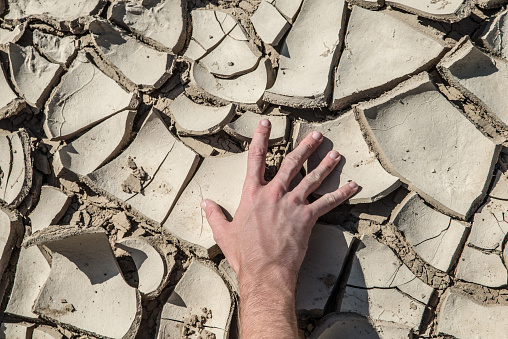 Hand on dry clay of a riverbed. Representation of dry global warming scenario