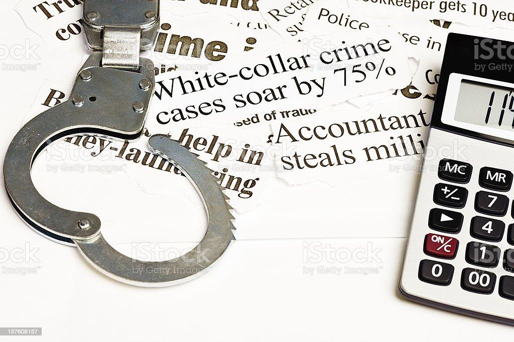 Open handcuffs and calculator on white collar crime headlines stock photo