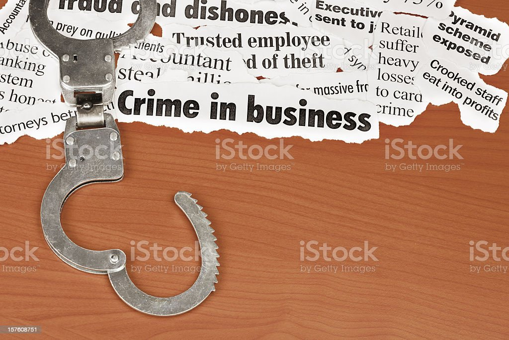 Open handcuffs next to headlines about business crime on desk stock photo