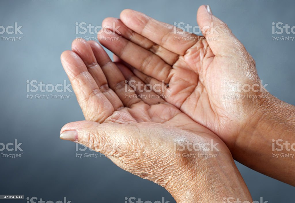 Open hands of mature person in front of grey background stock photo