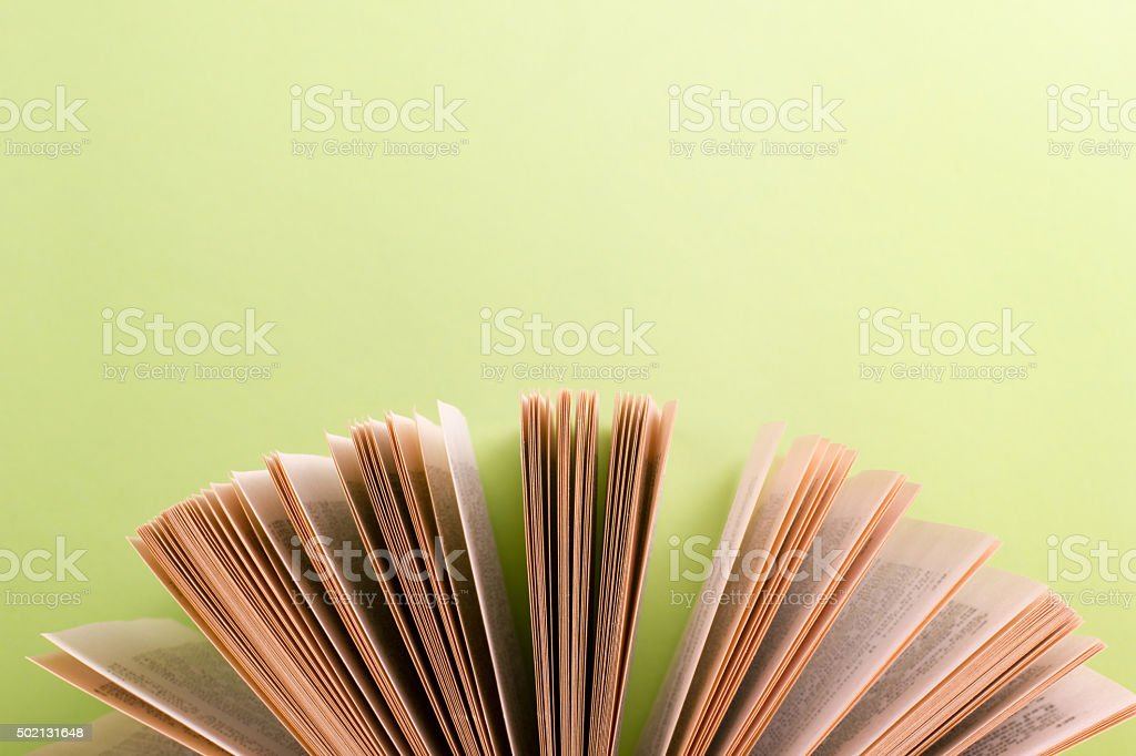 Open hardback book on wooden table and green background stock photo