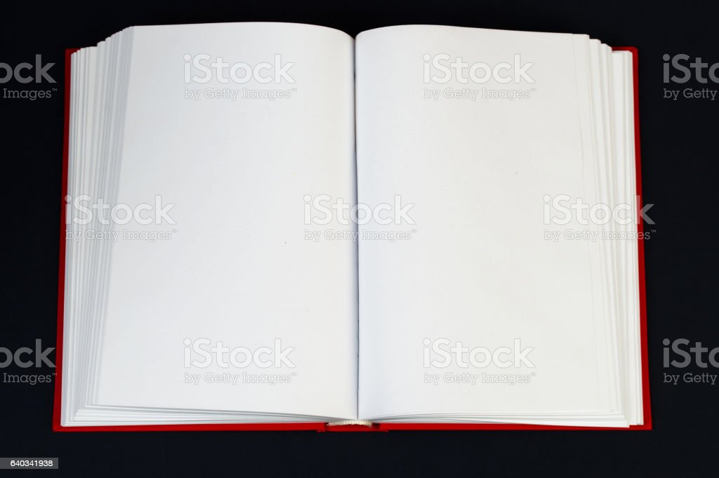 Open hardback book on wooden table. stock photo
