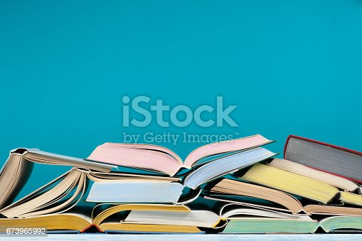 istock Open hardback colorful books on blue background. Back to school. Copy space for text. Education business concept 673965992