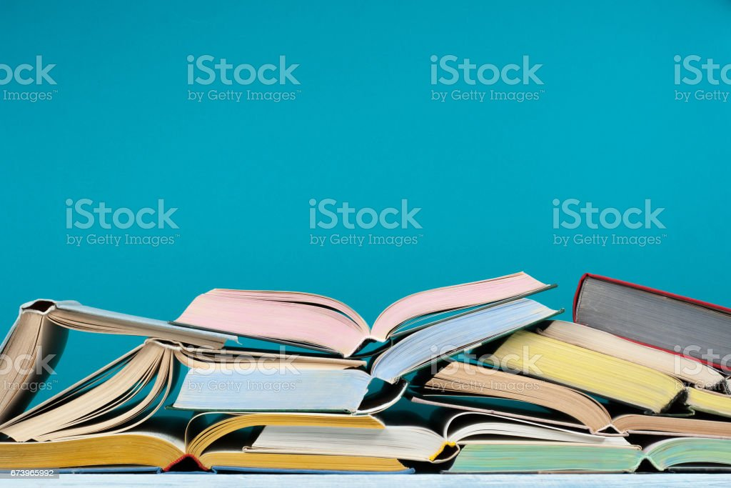Open hardback colorful books on blue background. Back to school. Copy space for text. Education business concept stock photo