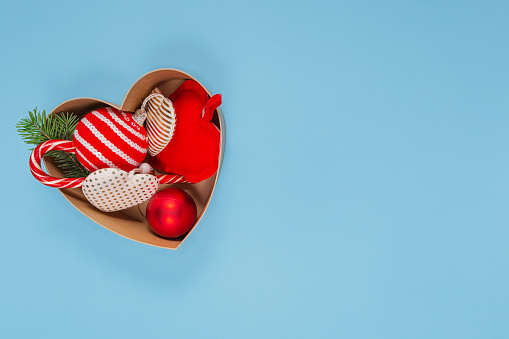 Open heart shaped box with Christmas decorations on a light blue background. There is a place for the text. Christmas and New Year concept.