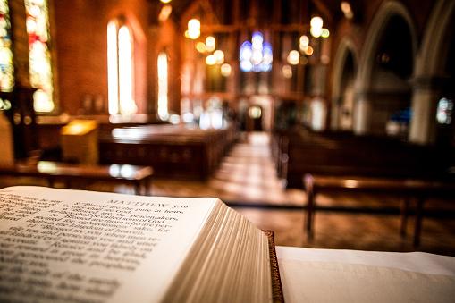 Open Holy Bible on Altar inside illuminated church