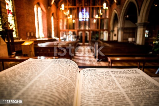 Close up color image depicting the Holy Bible book open on an altar inside an illuminated Anglican church. The book is open to one of the passages of the gospels. Focus is on the book in the foreground, while the interior architecture of the church is defocused beyond, with wooden pews and stained glass windows receding into the distance. Room for copy space.