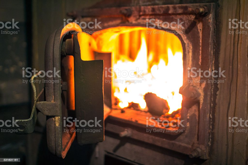 Open iron stove in boiler room stock photo