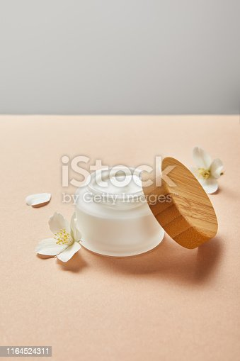 open jar with cream and wooden cap and few jasmine flowers on beige isolated on grey