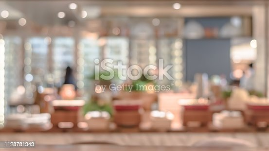 istock Open kitchen blur background in luxury hotel restaurant facility showing chef cooking over blurry food counter for buffet catering service 1128781343