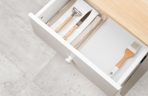 Open kitchen drawer with towels, different cutlery and copy space