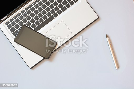 615494694 istock photo Open laptop and mobile on blue. Business concept. Top view. Copy space. 935978982