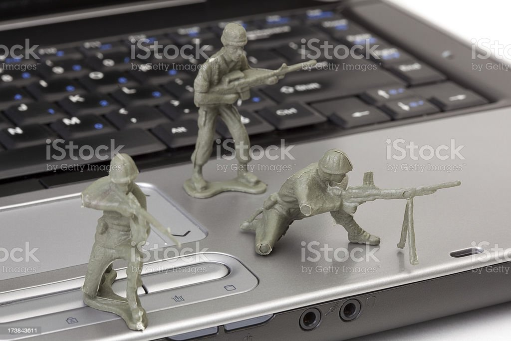 Open laptop computer with toy soldiers stock photo