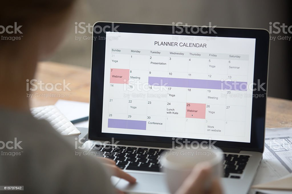 Open laptop on the desk, planner calendar on the screen - foto de acervo