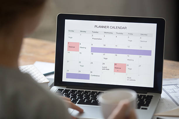 Open laptop on the desk, planner calendar on the screen stock photo