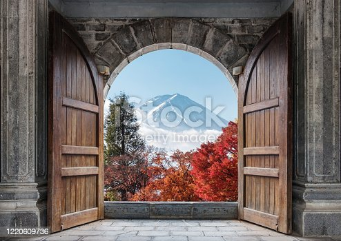 Open large wooden door with mount Fuji-san and autumn maple tree in blue sky at Japan