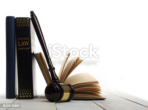 istock Open law book with wooden judges gavel on table in 504876992