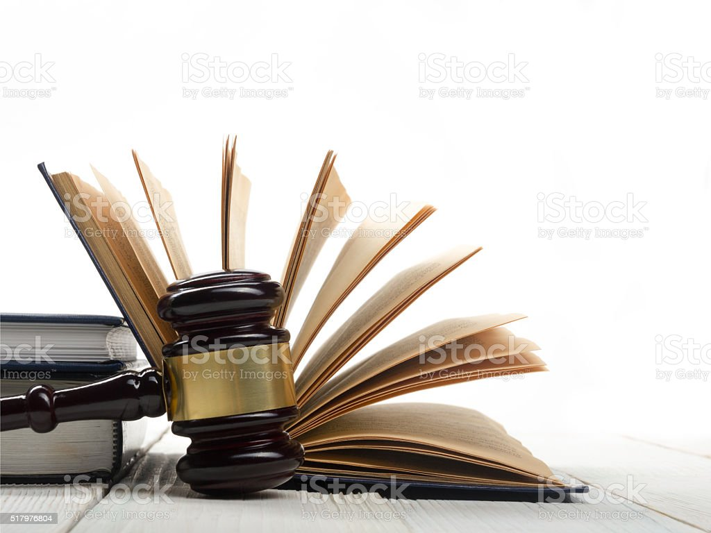 Open law book with wooden judges gavel on table in