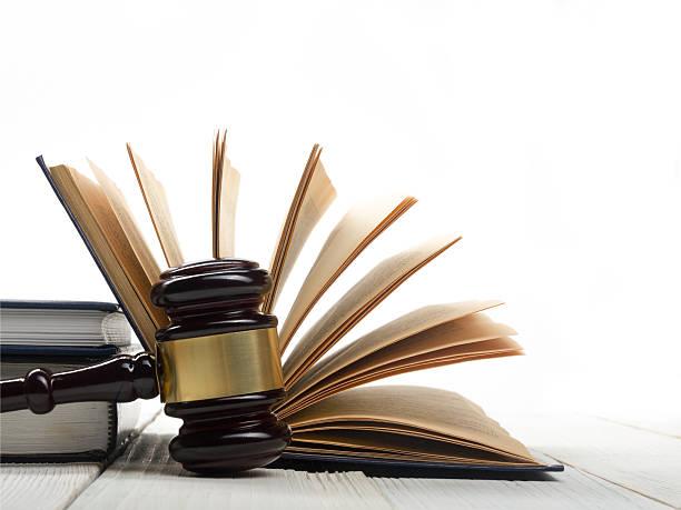 libro abierto con la ley de los jueces mazo de madera sobre la mesa en - legislación fotografías e imágenes de stock