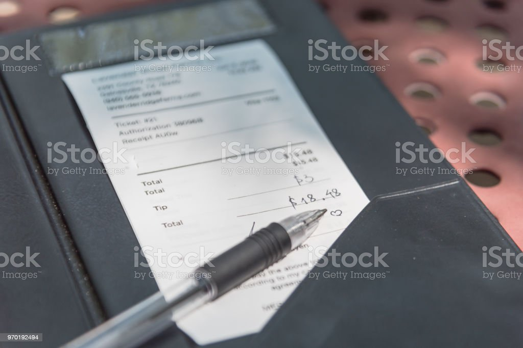 Open leather bill holder with restaurant check and pen. Soft focus...