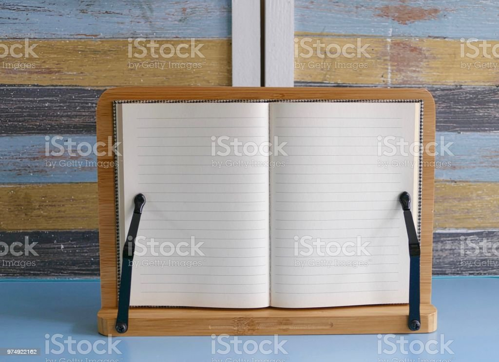 Open lined diary on bookend and multi colored wooden background