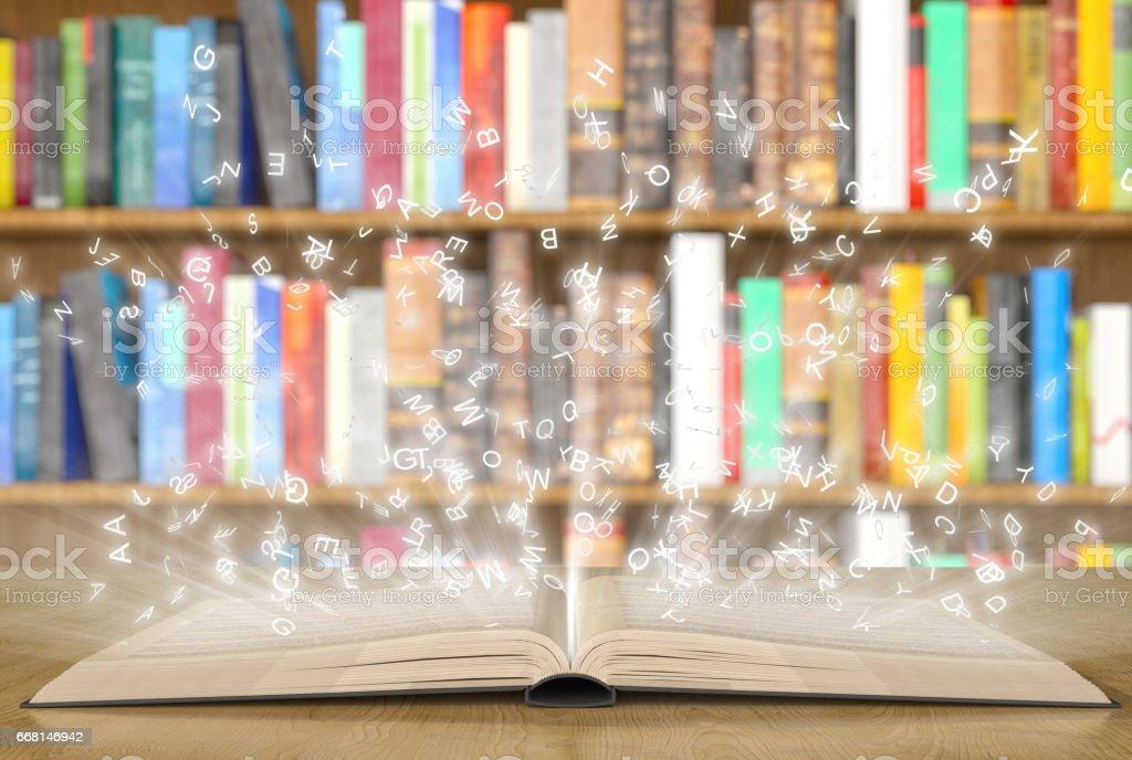 Open magic book with magic lights on a bookshelf stock photo