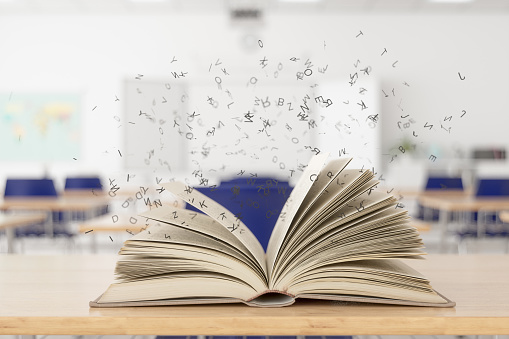 Open Magical Book On Desk In Classroom.