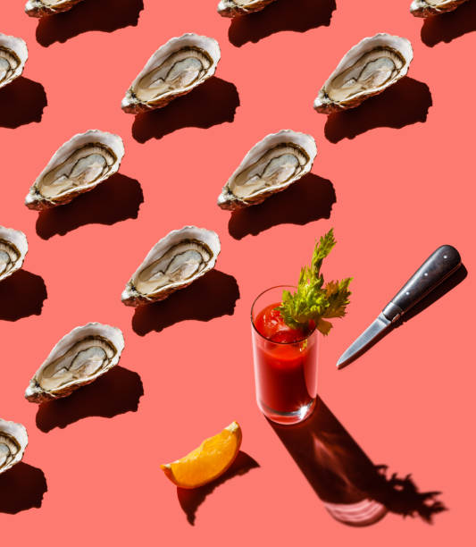 Open Mediterranean oyster and Bloody Mary cocktail on pink background Pattern stock photo
