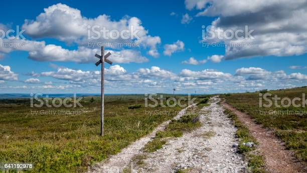 Photo of Open mountain landscape with a walking trail in the foreground leading to the horizon. Blue sky with clouds.