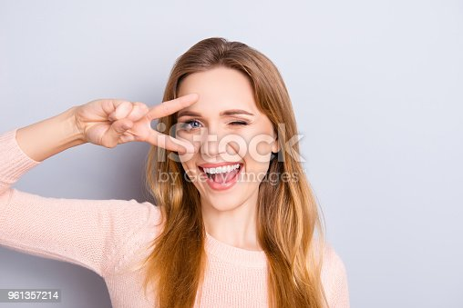 Open mouth people person entertainment concept. Close up portrait of playful excited funny joyful positive optimistic with toothy smile girl showing v-sign isolated on gray background copy-space