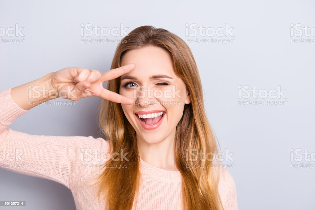 Open mouth people person entertainment concept. Close up portrait of playful excited funny joyful positive optimistic with toothy smile girl showing v-sign isolated on gray background copy-space stock photo