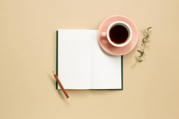 Open note book with cup of coffee on beige background. flat lay, top view, copy space stock photo