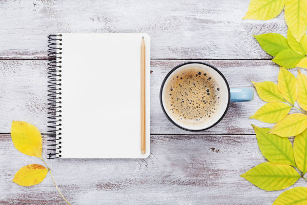 Open notebook and morning cup of coffee on rustic wooden table top view. Cozy autumn breakfast. Fall bucket list. Flat lay. stock photo