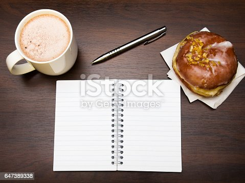 istock Open notebook, donut and cup of coffee on wooden table, 647389338
